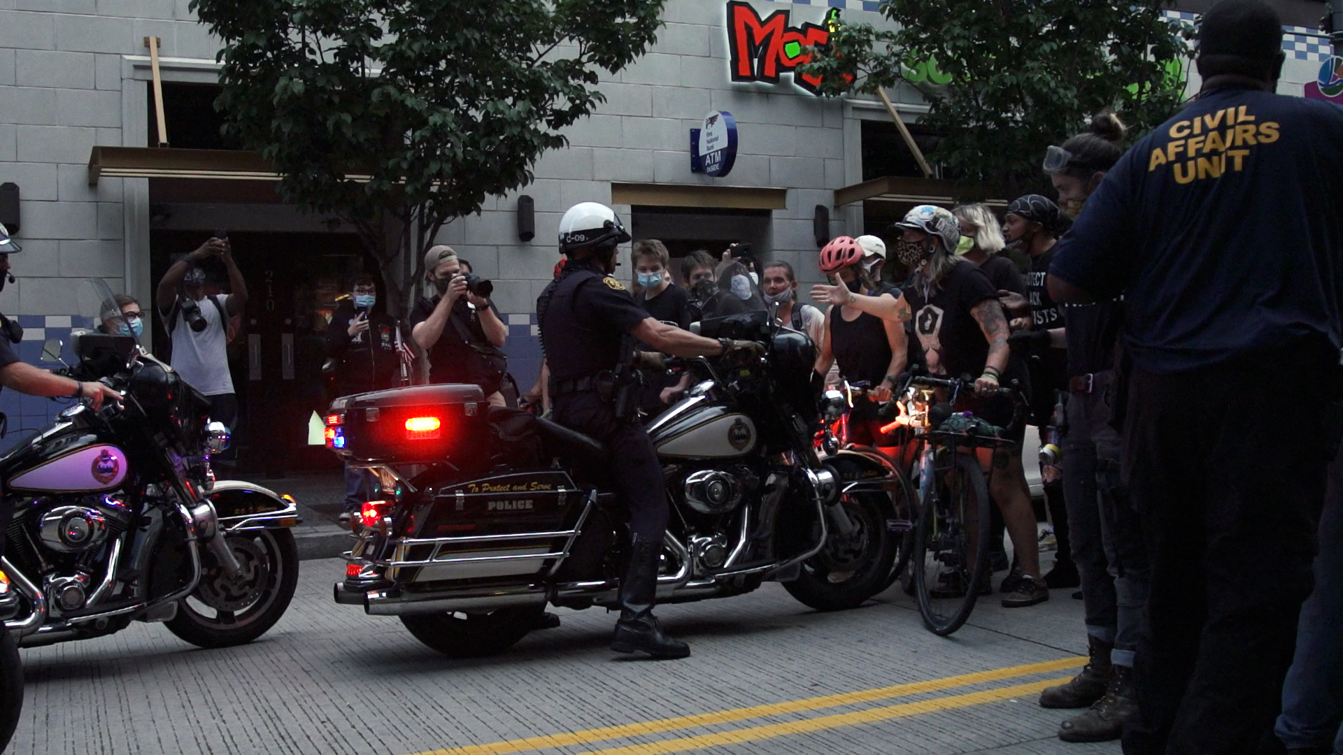 Police officer on motorcycle rolls into a protester on a bicycle who is standing in the street.