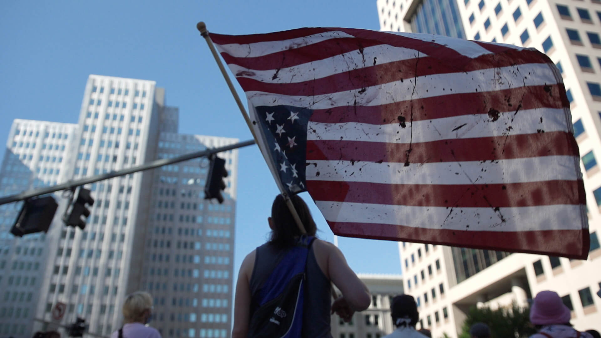 A demonstrator holds an upside down American flag as protesters circle around the intersection of Stanwix Street and Liberty Avenue in downtown Pittsburgh on Sept. 5.